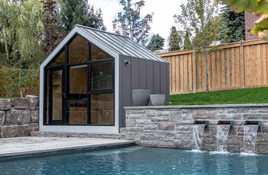 A modern bunkie is used as a poolside cabana