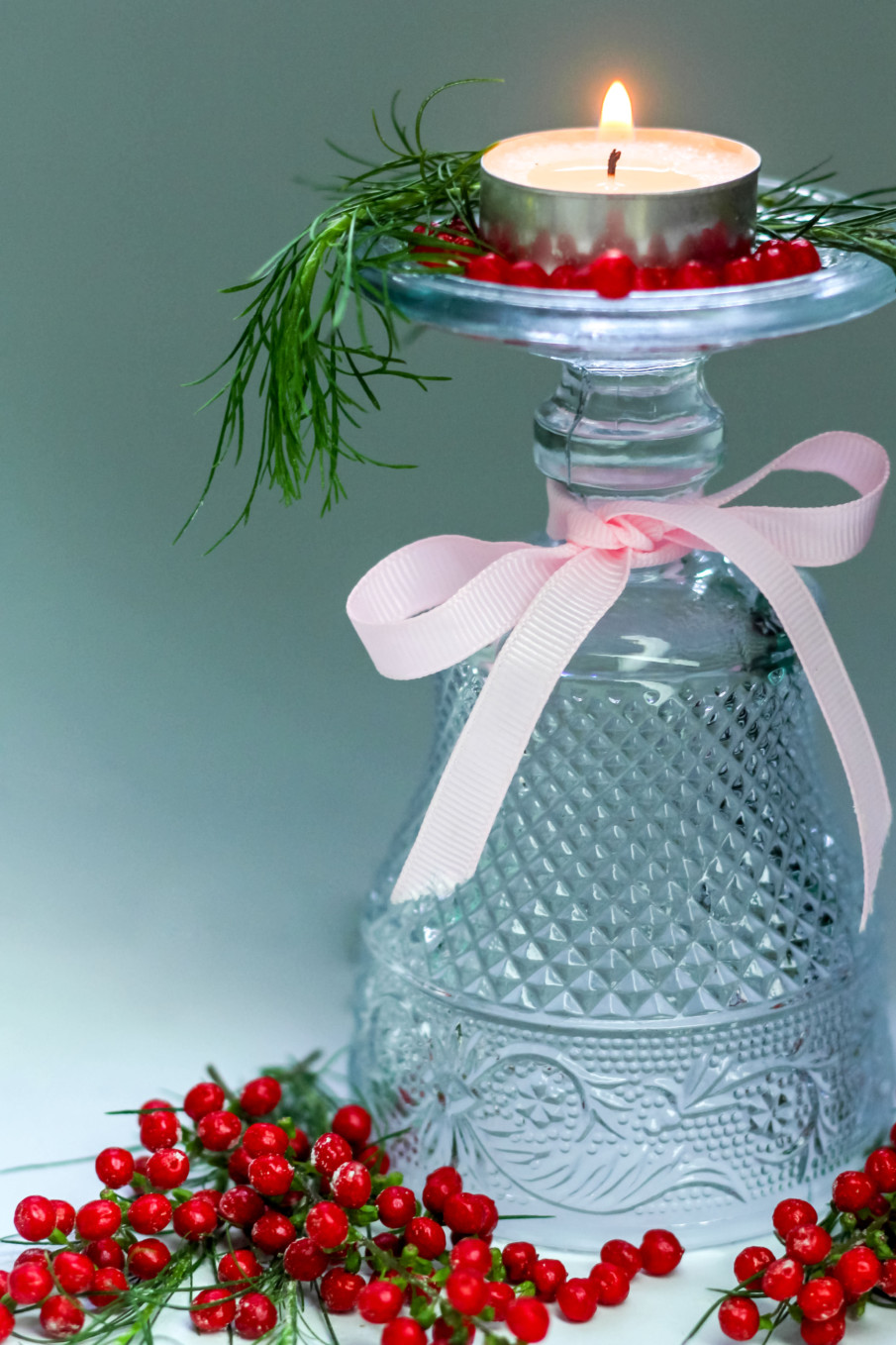 Centerpieces with candles idea using glass bottle, tealight candles, and red berries