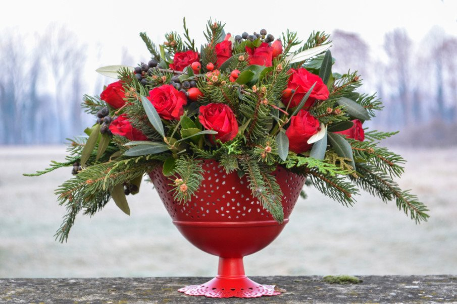 Traditional decor idea using fir tree stems and roses in red pedestal vase