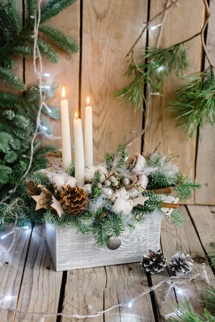 Clever tabletop centerpiece idea using a repurposed drawer with white candles and snowy boughs