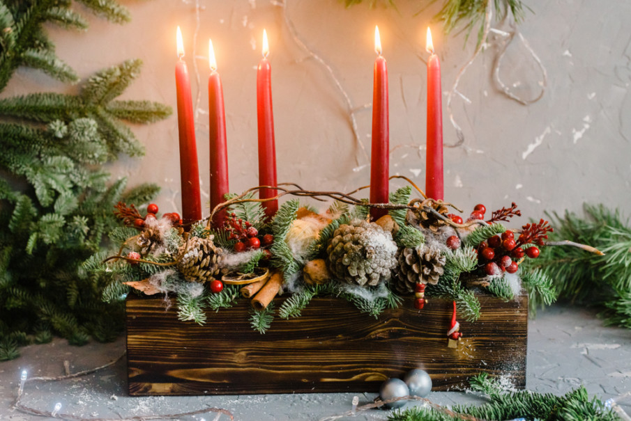 Farmhouse style tabletop decoration using distressed wood box and five red taper candles