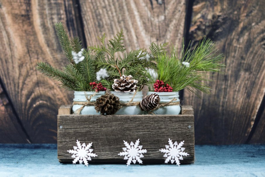 Three jars placed in a rough-hewn box with holiday touches like snowflakes and berries