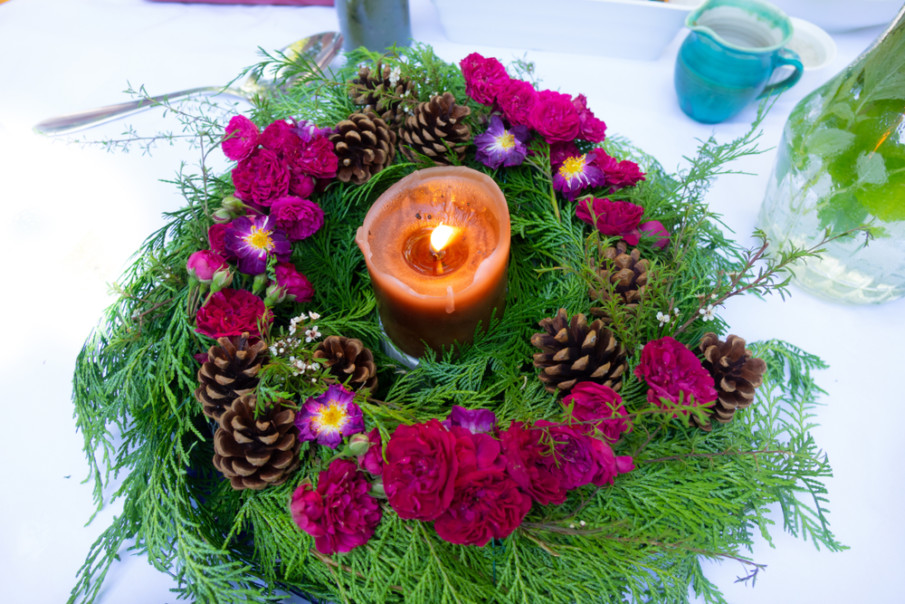 Create a festive Christmas centerpiece from cedar branches, magenta flowers, and pine cones