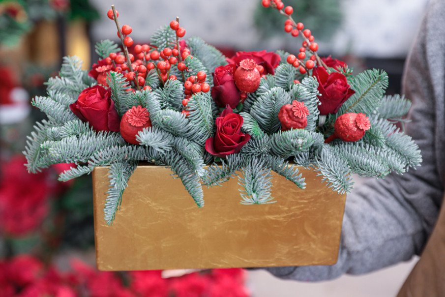 Holiday centerpiece with wood planter, blue spruce branches, red roses and holly berries