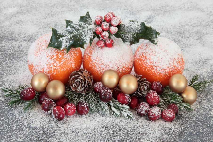 Christmas centerpiece ideas with cranberries and oranges dusted with snow on fir branches