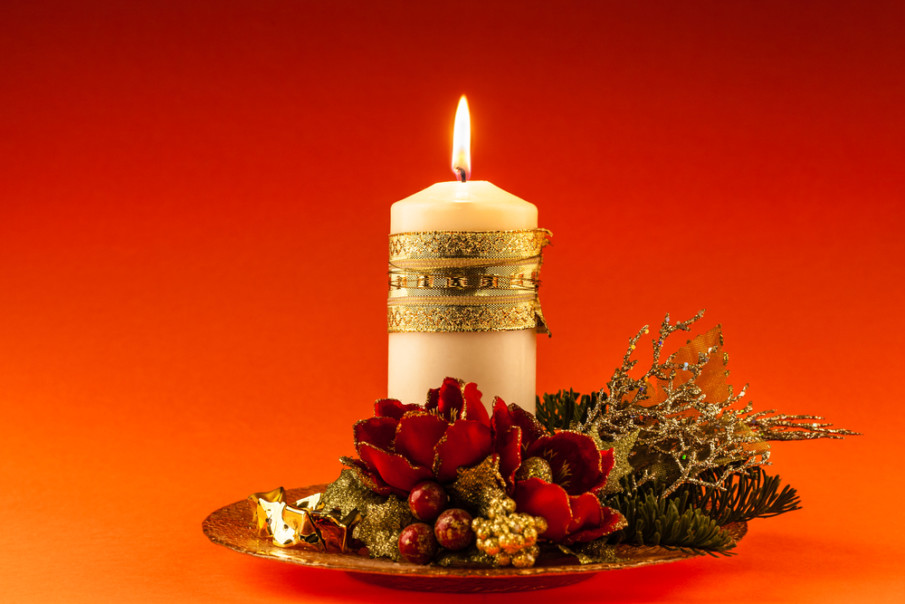 Red flowers, berries, fir branches and sprigs of greenery surround a gold ribbon wrapped candle