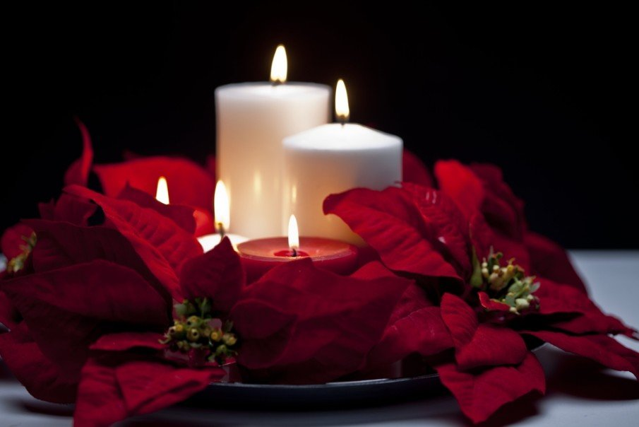 Timeless centerpieces with candles idea using a combination of pillar and votive candles with poinsettias