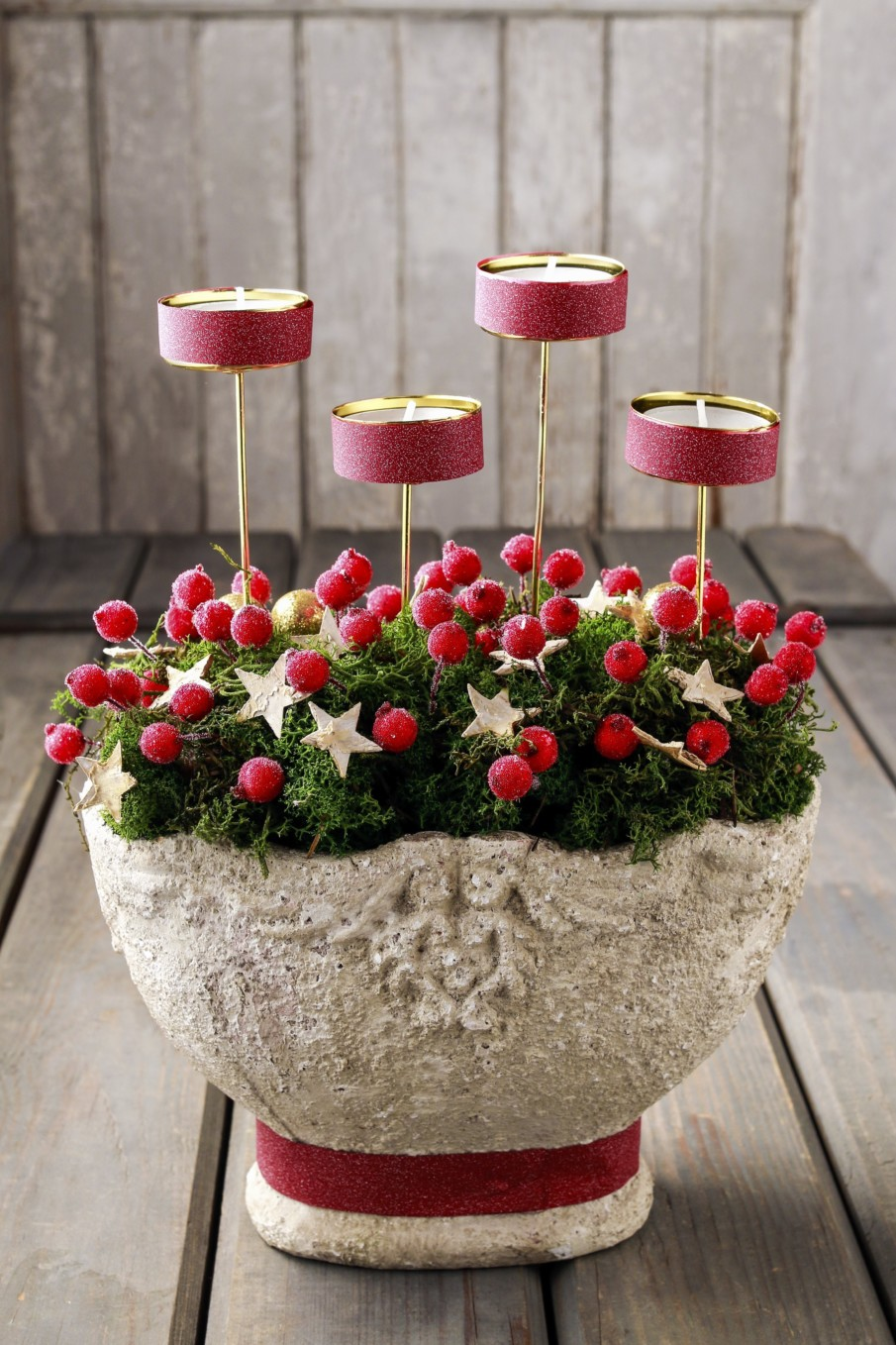 Centerpieces with candles ideas with red votives, pine branches and red berries in decorative planter