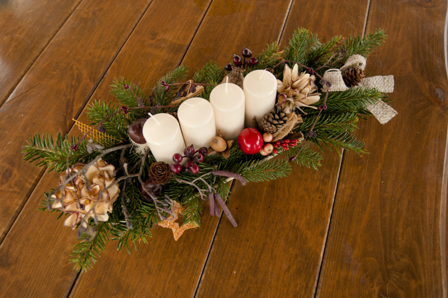 Rustic holiday centerpiece reflecting a winter forest - a mix of seasonal greenery with candles