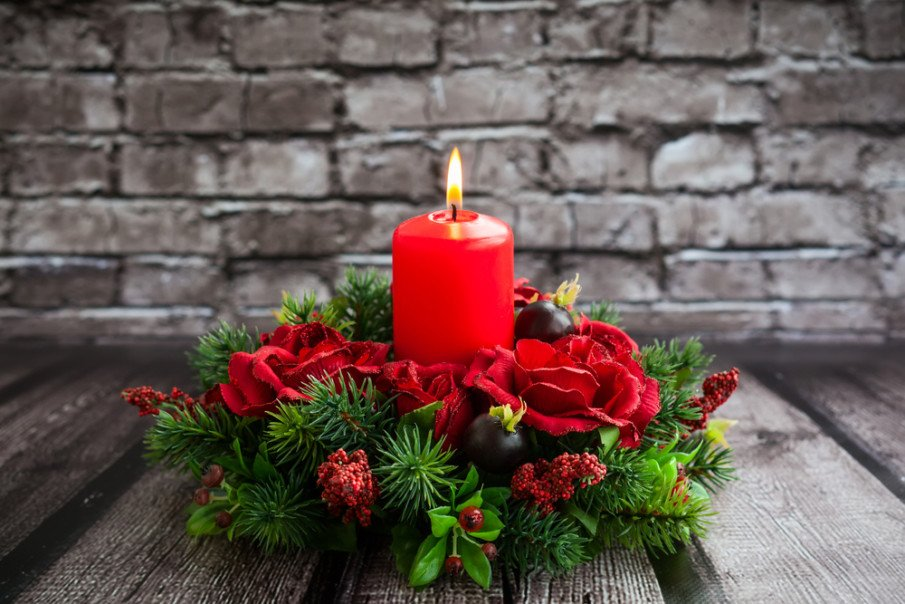 Seasonal tabletop decoration with red flowers, a red pillar candle and Christmas greens