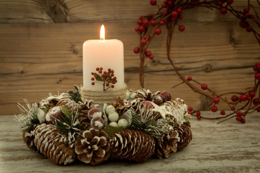 Centerpieces with candles idea for a pillar candle placed inside a wreath of pine cones, berries and evergreen stems