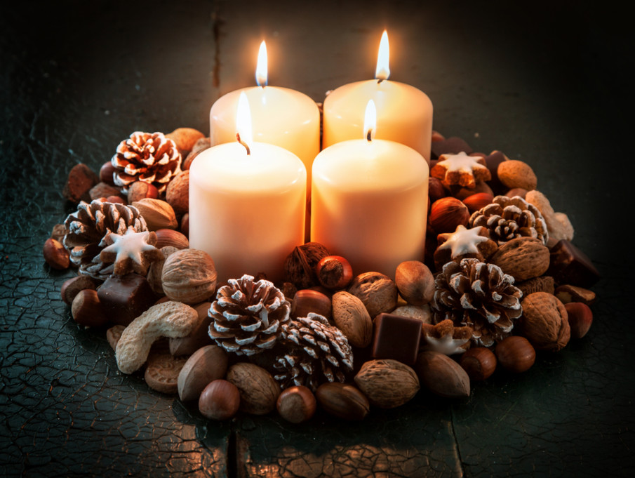 Four pillar candles surrounded by a Christmas wreath made of pine cones and nuts