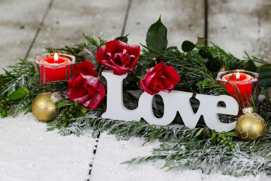 Christmas centerpiece with greenery, votive candles, red roses and a little love