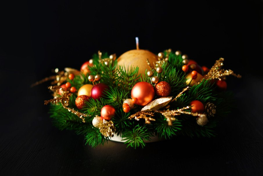 Christmas table decoration using holiday greens, gold and orange ornaments and berries