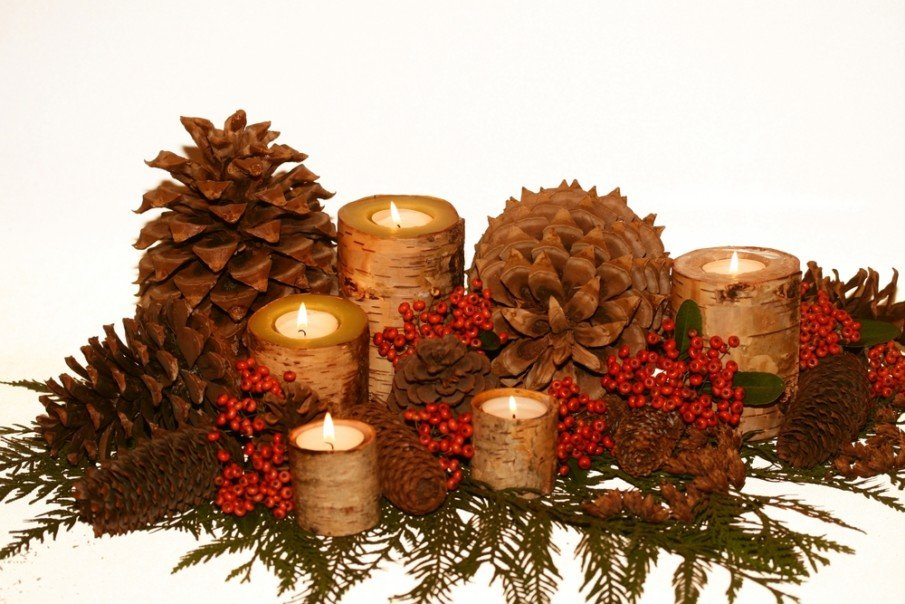 Birch bark candle holders, pine cones, and pyracantha berries in evergreens centerpiece idea