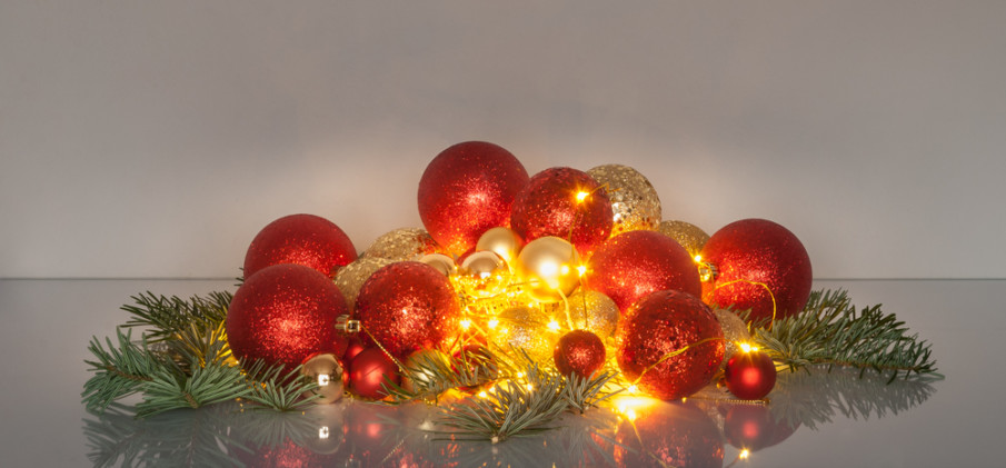 Add fairy lights to your centerpiece of red ornaments and holiday greens
