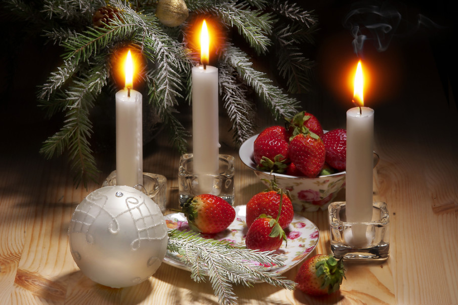 Frosted pine stem on plate with fresh strawberries surrounded by candles in glass holders