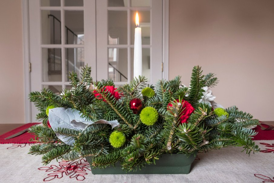 Christmas table centerpiece using assorted pine branches with flowers and ornaments