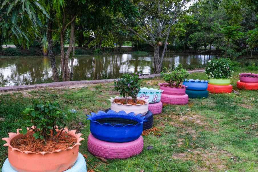 inverted tire flower pots in front of a pond