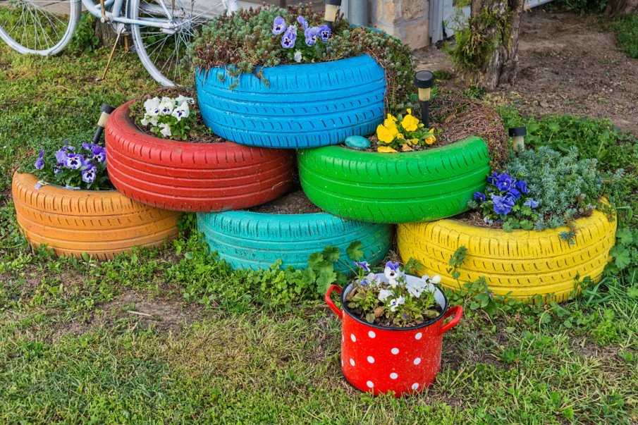 painted tire planters in a garden filled with flowers
