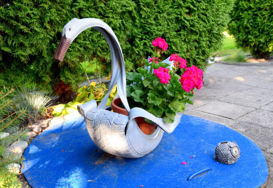 swan shaped tire planter with flowers