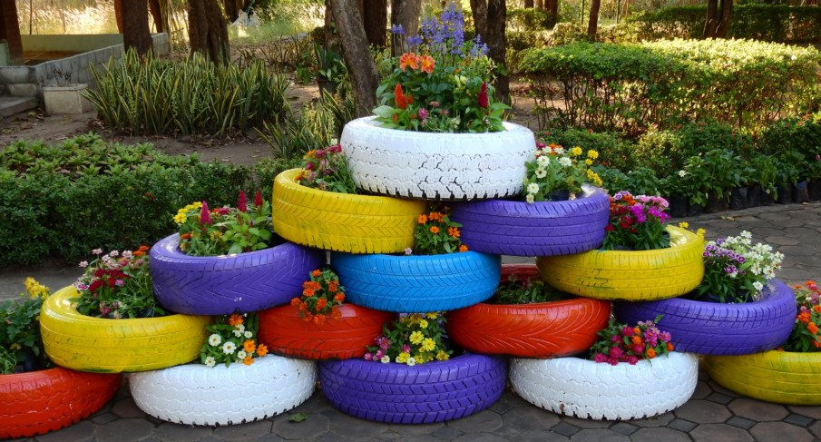 big pyramid of tire planters filled with flowers in a garden