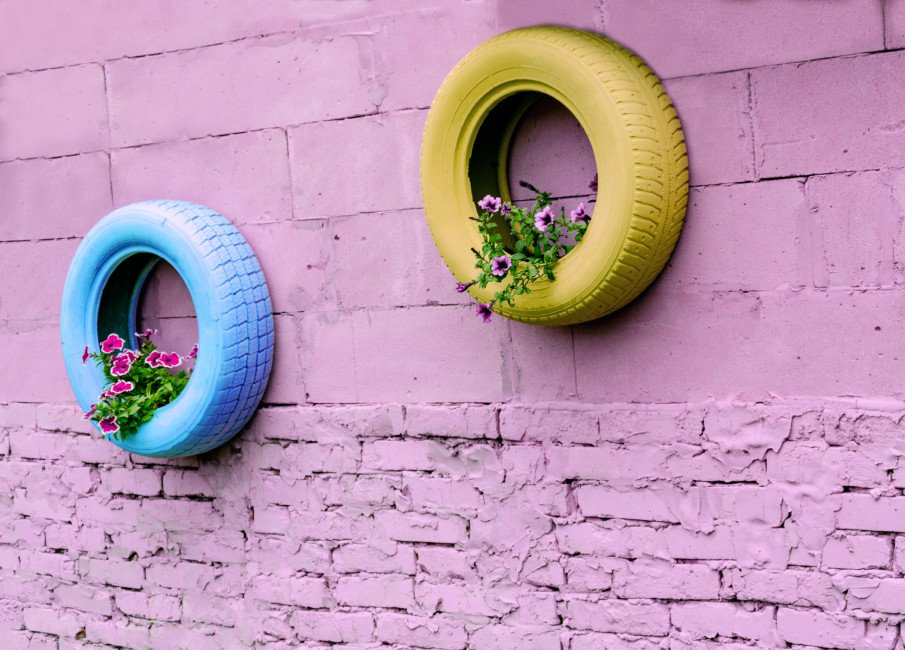 pink wall with pastel tire planters and flowers