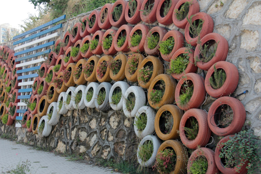 stone wall covered with tire planters