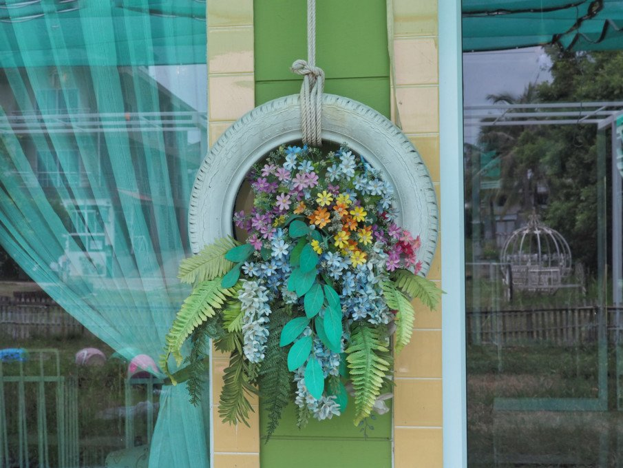 hanging tire planter filled with blooms in front of a window