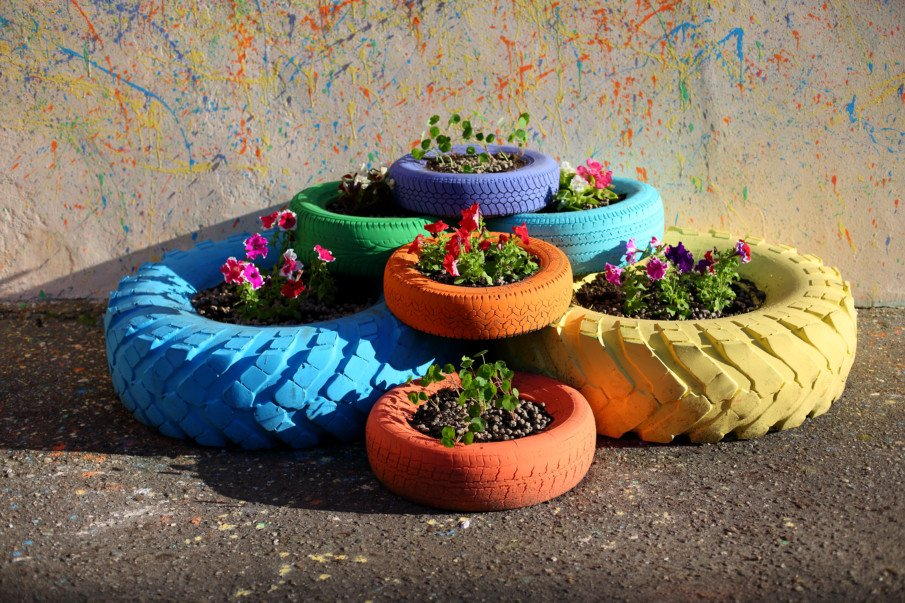 stacks of mixed size painted tire planters filled with flowers