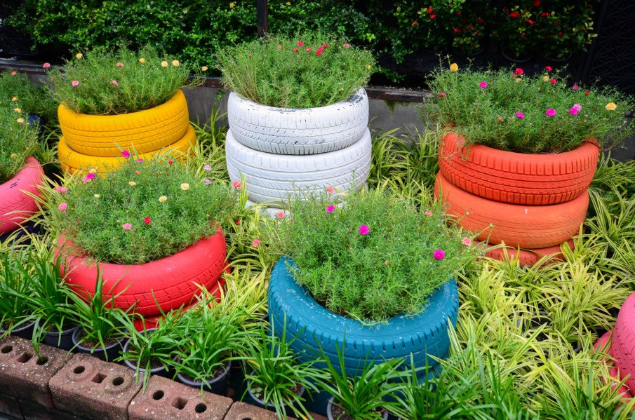 multiple stacked tire flower pots in a garden bed, painted in bright colors