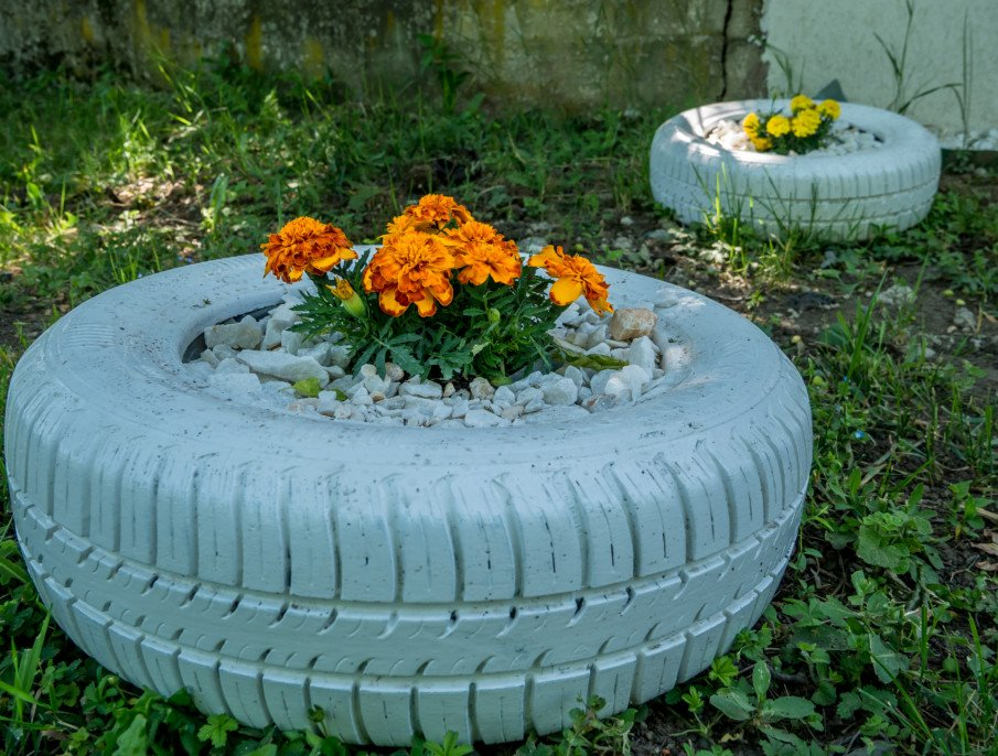 tire planter filled with small stones and flowers