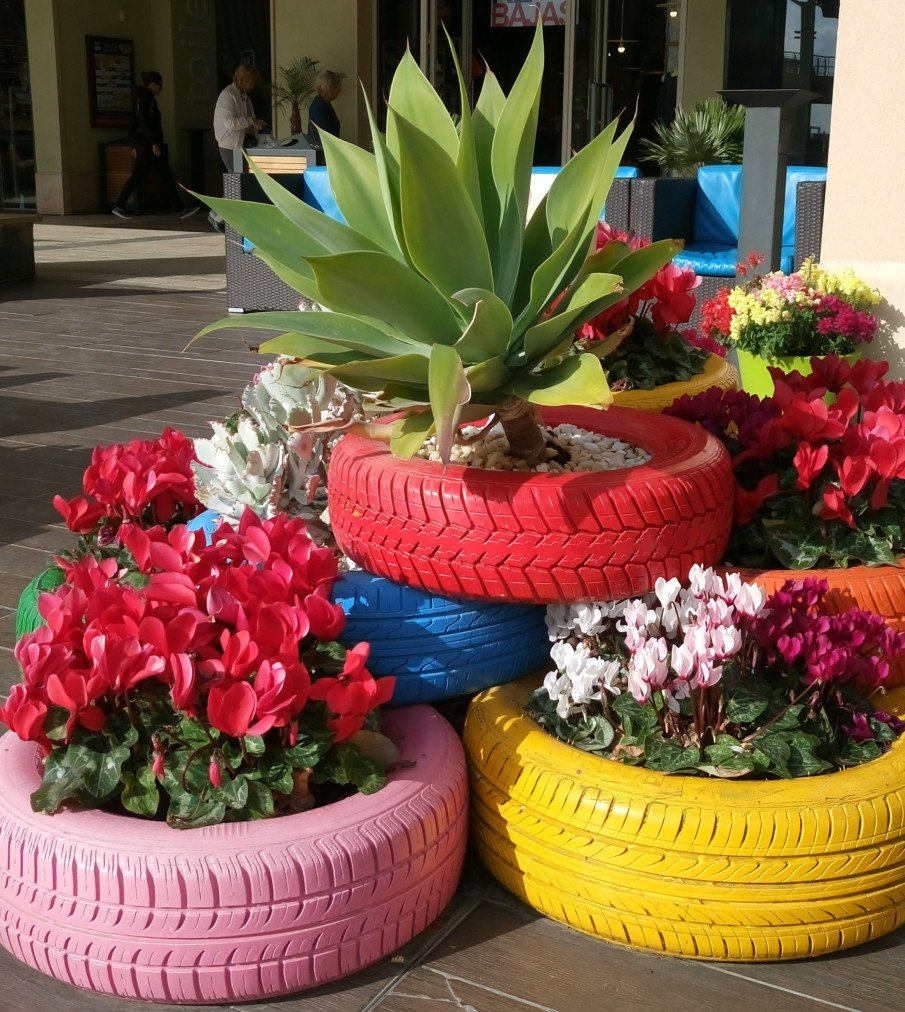 stacked painted tire planters with flowers and a large succulent