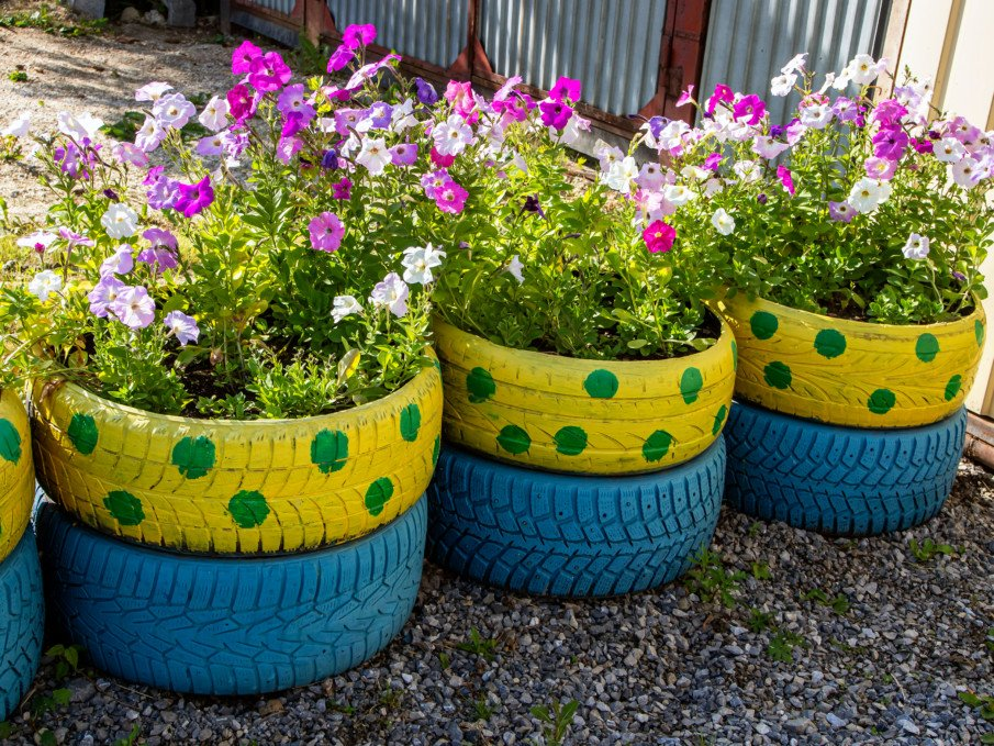 low wall of stacked tire flower pots with fun patterns