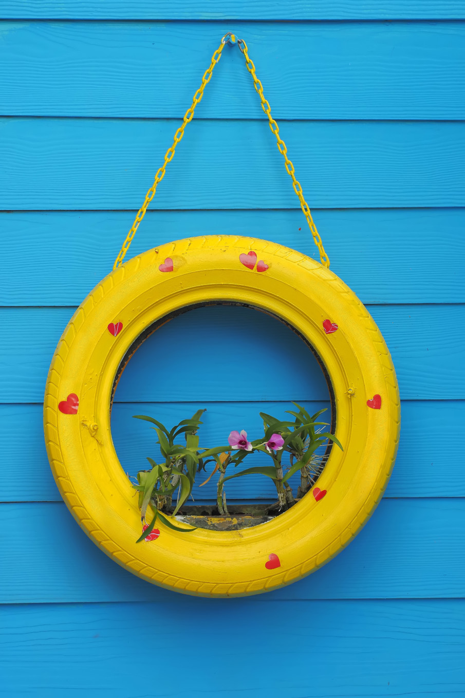 hanging tire planter with bamboo flowers