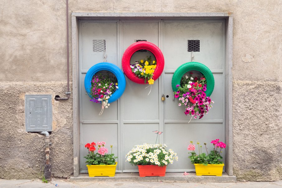 door with hanging tire planters and flower pots