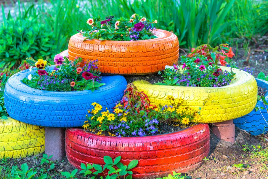 stacked painted tire planters filled with colorful flowers