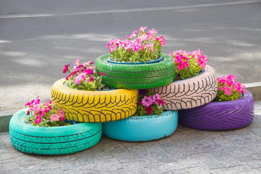 pyramid stacked tire planters with blooming pink flowers
