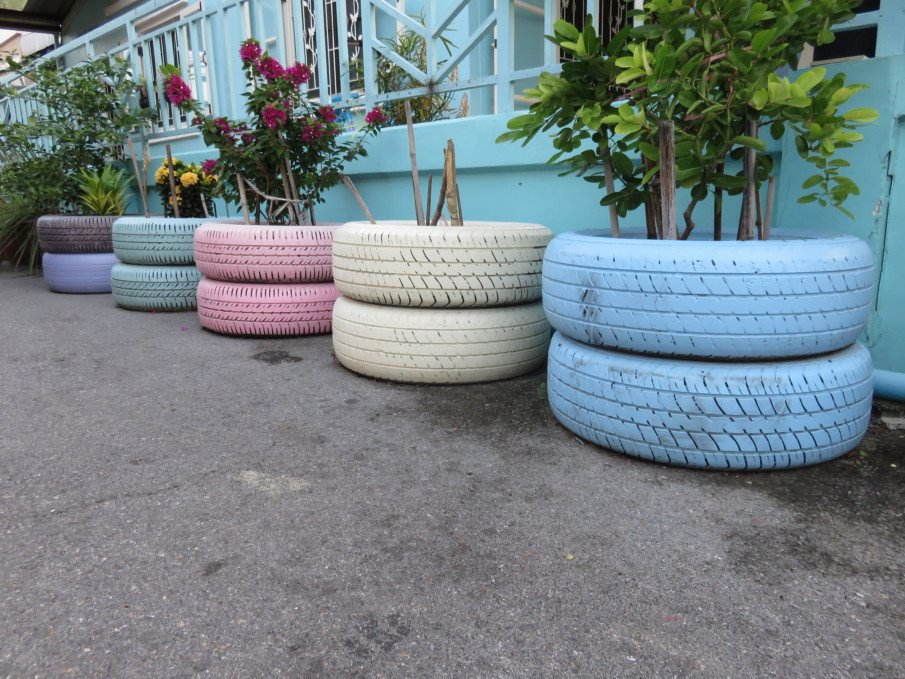 pastel painted stacked flower pots on a porch side