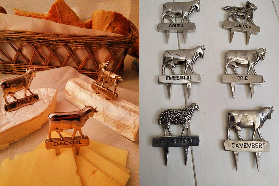 Vintage French markers label each cheese under the animal which produced it