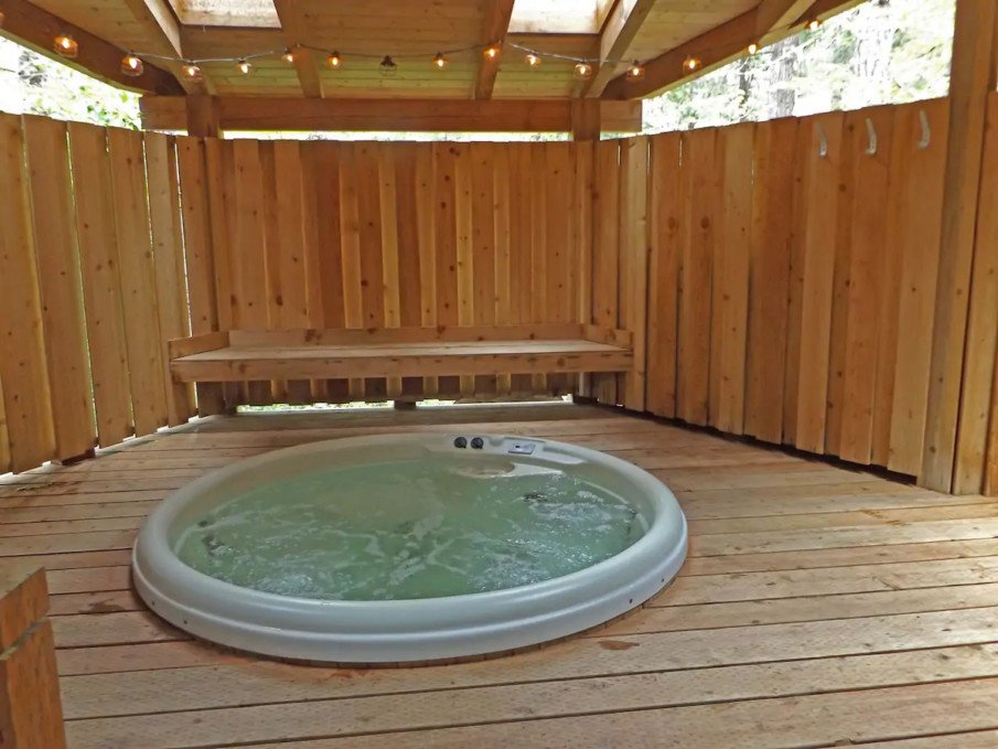 Custom fencing provides privacy for hot tub under a pergola