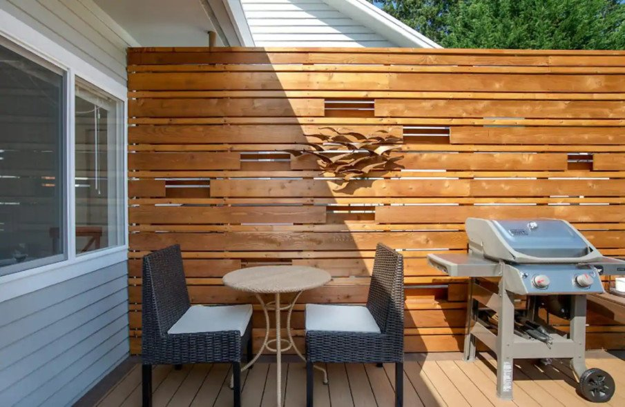 Decorative privacy wall for a hot tub installed on a deck