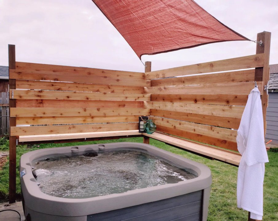Hot tub encloure created by corner wall and shade sail