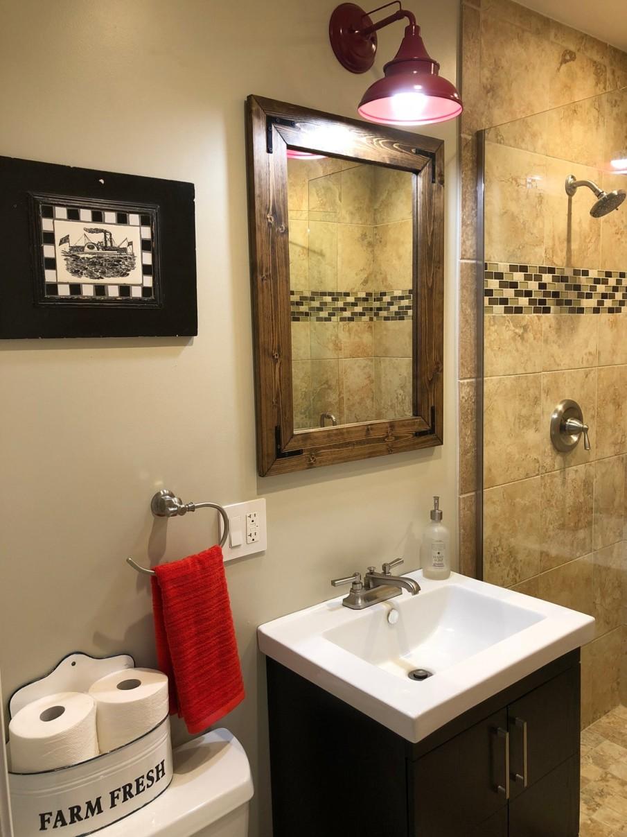 Rustic wooden mirror with metal fixtures in bathroom