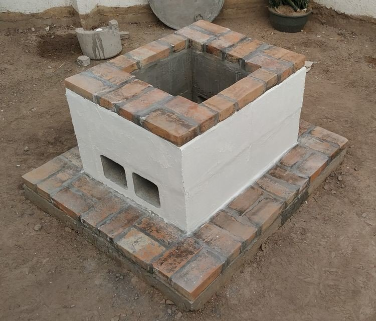 A cemented concrete block fire pit decorated with bricks