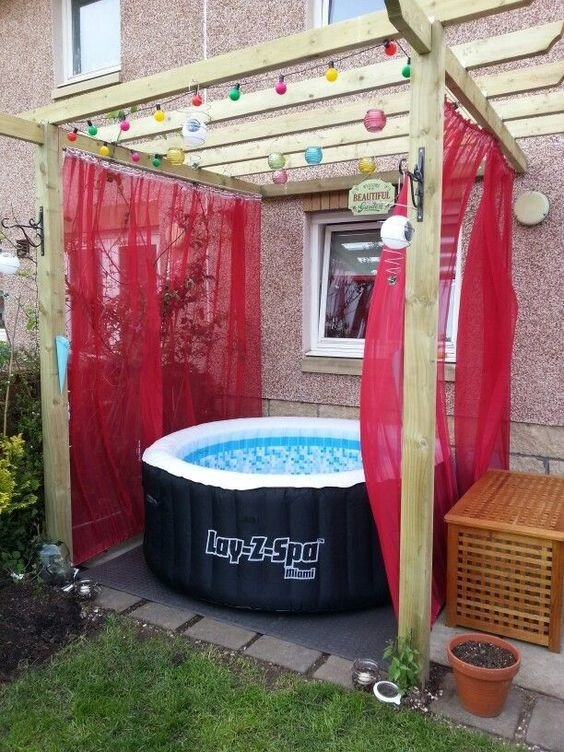 Red curtains give this simple wood hot tub pergola a splash of color
