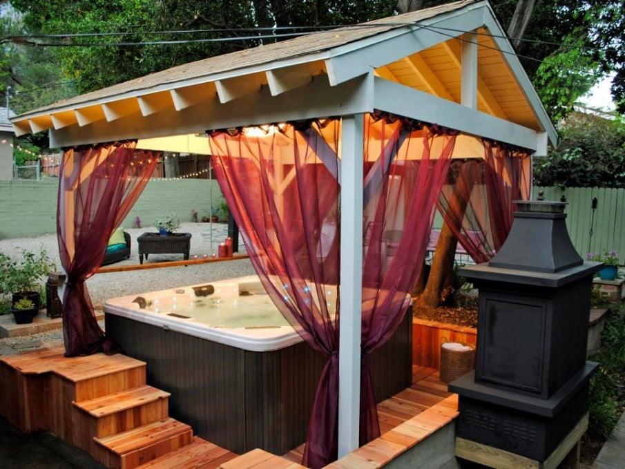 Sheer curtains hung from pergola create romantic hot tub atmosphere