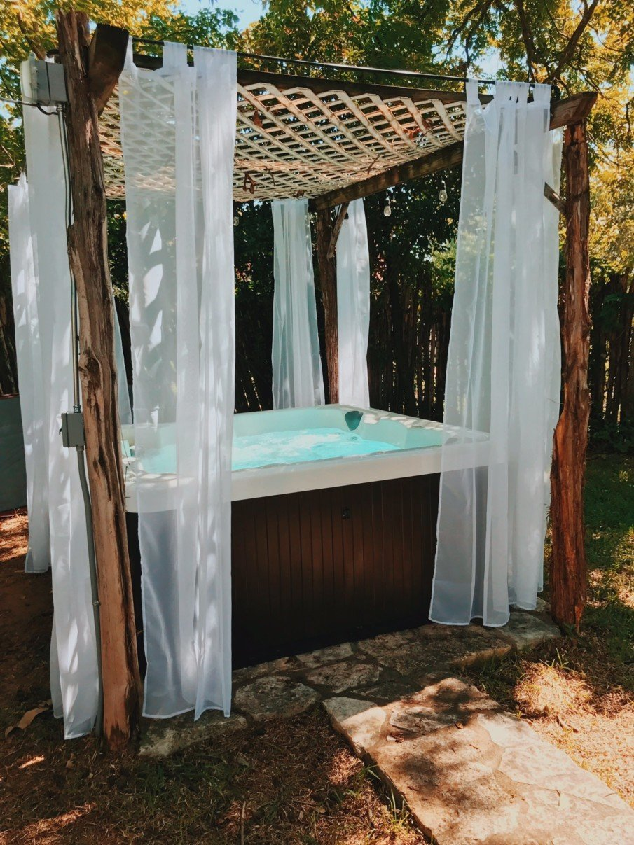 Cheap hot tub pergola with curtains has a rustic appeal