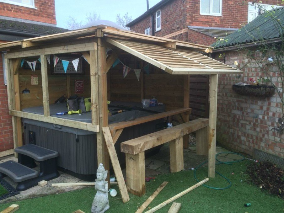 Hot tub pergola privacy idea with two solid wood walls and a lift-up side panel