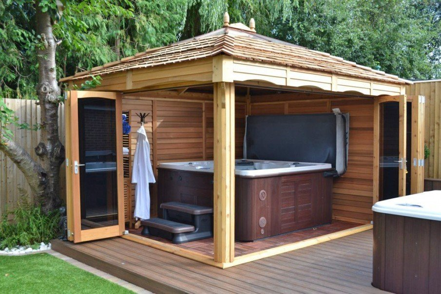 Hot tub pergola ideas with solid roof, wood privacy enclosure and folding glass doors